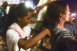 Cambodian girl cutting backpacker's hair